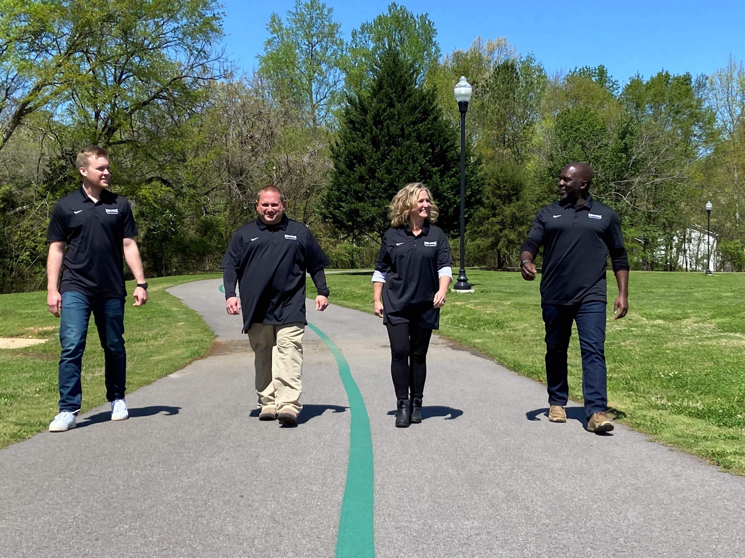 picture of park staff (three men and one woman) walking on a trail