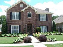 Two story brick house with grass lawn and sidewalk leading to front door.