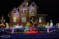 157 Lauchlin Lane, three story brick house, at night, with Christmas lights in yard and on house